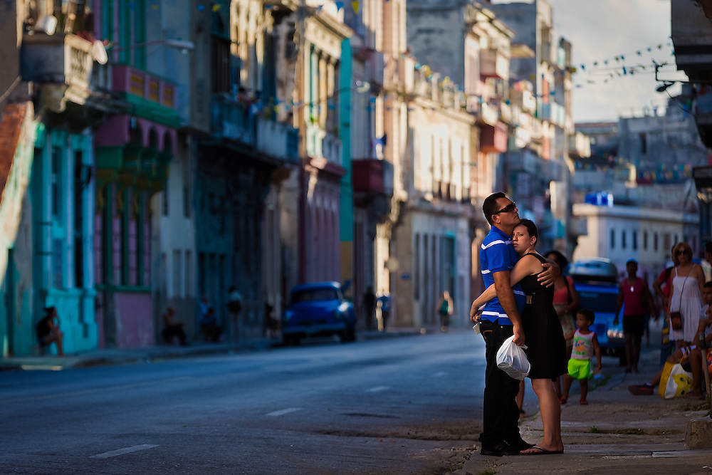 A man and woman stand in the street together while waiting for a bus in Central Havana.