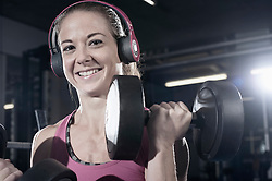 Portrait of a mid adult woman doing exercise with dumbbells in the gym and listening to music, Bavaria, Germany