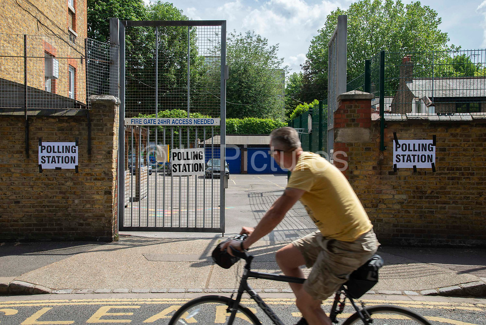 A man cycles past a polling station on 23rd May 2019 in Greenwich ,South- East London, England, United Kingdom. Polls are open for the European Parliament elections. Voters will choose 73 MEPs in 12 multi-member regional constituencies in the UK with results announced once all EU nations have voted. The voting process expected to be completed by 10pm on Sunday.