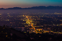 Twilight view of the San Fernando Valley with the San Gabriel Mountains behind, shot above Sherman Oaks from Mulholland Drive, Los Angeles, California USA.