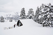 Skiers stand outside the Elfin Lakes Hut, a large shelter in Garibaldi Provincial Park, British Columbia, Canada.