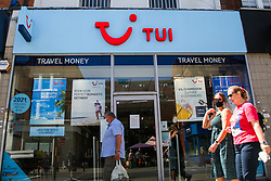 © Licensed to London News Pictures. 30/07/2020. London, UK. Members of public wearing a face coverings walk past a Tui store on Wood Green High Road in north London. Tour operator Tui announced that 166 high street stores in the UK and the Republic of Ireland will shut due to a downturn in travel caused by the coronavirus pandemic. Photo credit: Dinendra Haria/LNP