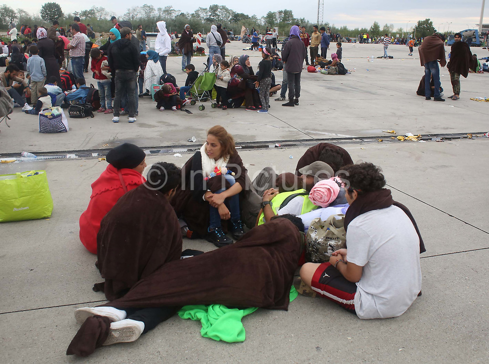 Migrants wait to board buses at the Austrian and Hungary border September 5, 2015.  Thousands of migrants crossed into Austria, after Hungary's surprise move to take them by bus to the border.