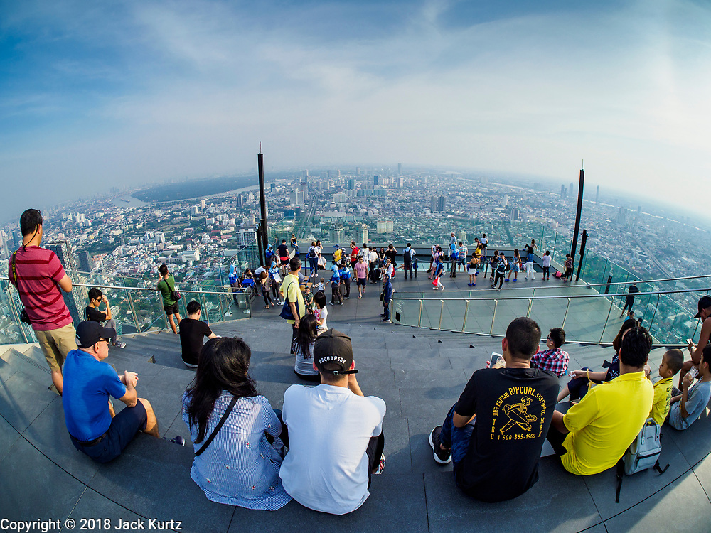 27 DECEMBER 2018 - BANGKOK, THAILAND:  TPeople on the rooftop observation deck of the King Power Maha Nakhon Tower. The MahaNakhon Skywalk, at the top of the King Power Maha Nakhon Tower, is 1,030 feet (314 meters) above street level. It is the tallest building and highest vantage point in Bangkok. The skywalk opened in November and has been drawing large crowds.    PHOTO BY JACK KURTZ