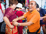 """15 OCTOBER 2014 - BANGKOK, THAILAND:  A shop owner rents a coverup to a Chinese tourist who was going to visit the Grand Palace. The Palace has a dress code and vendors in front of the palace rent """"sarangs,"""" a traditional Thai skirt, to tourists whose clothes are too revealing. The number of tourists arriving in Thailand in July fell 10.9 per cent from a year earlier, according to data from the Department of Tourism. The drop in arrivals is being blamed on continued uncertainty about Thailand's political situation. The tourist sector accounts for about 10 per cent of the Thai economy and suffered its biggest drop in visitors in June - the first full month after the army took power on May 22. Arrivals for the year to date are down 10.7% over the same period last year.   PHOTO BY JACK KURTZ"""