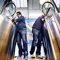 """Nederland, Amsterdam , 12 december 2013.<br /> Bierbrouwerij de Prael.<br /> Leer-werkbedrijf Brouwerij de Prael leidt dit jaar verlies. Zorggelden voor begeleiding nemen af en er is onvoldoende capaciteit om aan de vraag van een groeiende biermarkt te voldoen. """"Doorgroeien is noodzakelijk.<br /> De brouwerij die in 2008 vanwege een ruimtetekort naar de Oudezijds Voorburgwal verhuisde, lijkt nu opnieuw uit zijn voegen gegroeid. De verkoop loopt goed, het Proeflokaal loopt goed. Maar de ruim 130 werknemers met een psychiatrische achtergrond vergen begeleiding, en de zorggelden daarvoor nemen af. """"We krijgen van bijvoorbeeld DWI of GGZ instellingen een derde minder geld. De bijdrage voor individuele begeleiding is weggevallen."""" zegt Fer Kok, bedrijfsleider bij de brouwerij. Tien mensen blijken nu door de verplichte CIZ-indicatie niet te indiceren. De Prael krijgt daarvoor geen vergoeding en ontvangt een ton minder inkomsten per jaar. """"Doordat een vergoeding voor tien mensen wegvalt, draaien wij verlies. Toch wegsturen omdat ze hem niet hebben? Dat krijg ik niet over mijn hart. Over een jaar of drie komen ze dan terug met indicatie en al, maar zijn ze er stuk een stuk slechter aan toe.""""<br /> Op de foto: Bedrijfsleider Fer Kok (l) met 1 van de werknemers met psychiatrische achtergrond aan het werk in de brouwerij.<br /> Beer brewery Prael with employees who need care and learning as psychiatric patients, is loss-making this yea , due by cuts of care money necessary for the supervision."""