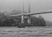 Saint-Georges de l'Oyapock, Guyane, 2015. <br />  <br /> Fleuve frontière et voie de communication naturelle entre les deux pays, l'Oyapock sépare la Guyane du Brésil. Ici, les riverains sont géographiquement, mais aussi culturellement ou économiquement plus proches de la rive opposée que de leurs capitales régionales. La France et le Brésil travaillent pourtant à l'achèvement d'une liaison routière qui reliera de façon terrestre la Guyane française à l'État brésilien de l'Amapà et plus globalement l'Union Européenne au Mercosul.  <br />  <br /> La construction d'un pont de 378 mètres de long entre Saint-Georges et Oiapoque devrait permettre le passage du fleuve.  Projet initié en 1997 par le président Jacques  Chirac  et  son   homologue brésilien Fernando Henrique Cardoso, cet ouvrage a mis des années à voir le jour. Sa construction n'a débuté qu'en 2008 et s'est achevée en 2011. Depuis, les travaux de ses voies d'accès ou la signature d'accords transfrontaliers entre la France et le Brésil s'éternisent et il n'est toujours pas ouvert à la circulation.  <br />  <br /> Il s'érige maintenant en barrière sur un territoire difficilement contrôlable et transforme un espace de libre passage en zone douanière. Avec sa mise en service, il va falloir bloquer les marchandises non conformes aux normes européennes et les voyageurs clandestins, c'est à dire l'essentiel du trafic. <br />  <br /> Pendant qu'au pied du pont, coté guyanais, un effectif renforcé d'une soixantaine d'agents de la Police aux frontières française patientent, jour et nuit, légaux ou clandestins, orpailleurs, amérindiens et autres refoulés continuent de passer par le fleuve.