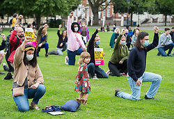 "© Licensed to London News Pictures; 07/07/2020; Bristol, UK. Protestors ""take the knee"" in commemoration and respect at a protest organised by Stand Up to Racism Bristol for ""No Prosecutions over Colston Statue"" taking place on College Green in front of City Hall. The protest opposing any prosecutions of people who toppled the statue of Edward Colston and threw it into the water at Bristol Harbourside is taking place just before a Bristol city council meeting where a motion is due for debate calling on the Government to set up a commission to acknowledge, apologise and instigate amends for wrongs that still have an impact today, and asking Labour mayor Marvin Rees to lead the city in lobbying Westminster for an all-party parliamentary inquiry. The motion was tabled by Green Party councillor and former Bristol lord mayor Cleo Lake who was also a founding member of the Countering Colston group, which has campaigned for the city to dismantle its public celebration of slave trader Edward Colston. The statue of Edward Colston was toppled from its plinth and thrown into Bristol Harbour during a Black Lives Matter protest rally and march on 07 June in memory of George Floyd, a black man who was killed on May 25, 2020 in Minneapolis in the US by a white police officer kneeling on his neck for nearly 9 minutes. Police in Bristol are seeking to identify 18 people in connection with what police say is criminal damage to the statue. The killing of George Floyd has seen widespread protests in the US, the UK and other countries, despite the restrictions due to the Covid-19 coronavirus pandemic. Today's event is organised by Stand Up to Racism Bristol and due to the coronavirus pandemic participants are advised of the need to wear masks and maintain social distancing to avoid the spread of the virus. Photo credit: Simon Chapman/LNP."