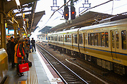 Commuters on the platform at Osaka train station, Osaka Japan
