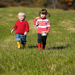 A young brother (age 2) and sister (age 4) explore a field on the Common Pasture in Newburyport, MA.