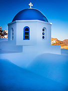 Iconic blue domed chapel in the town of Oia on the greek island Santorini (Thera). Santorini, classically Thera and officially Thira, is an island in the southern Aegean Sea, about 200 km (120 mi) southeast of Greece's mainland. It is the largest island of a small, circular archipelago which bears the same name and is the remnant of a volcanic caldera. It forms the southernmost member of the Cyclades group of islands. The municipality of Santorini includes the inhabited islands of Santorini and Therasia and the uninhabited islands of Nea Kameni, Palaia Kameni, Aspronisi, and Christiana. Santorini is essentially what remains after an enormous volcanic eruption that destroyed the earliest settlements on a formerly single island, and created the current geological caldera. A giant central, rectangular lagoon is surrounded by high, steep cliffs on three sides.