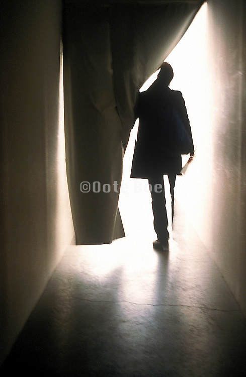 Man silhouetted against bright light as he walks through curtain