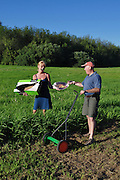 """Humorous photograph of a man mowing a large field with a hand mower and a woman handing him a picture of a wok cut out of a box visually depicting the saying """"You've got your wok (work) cut out for you!"""""""