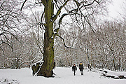 Two men walk across snow-covered Hampstead Heath, North London, United Kingdom