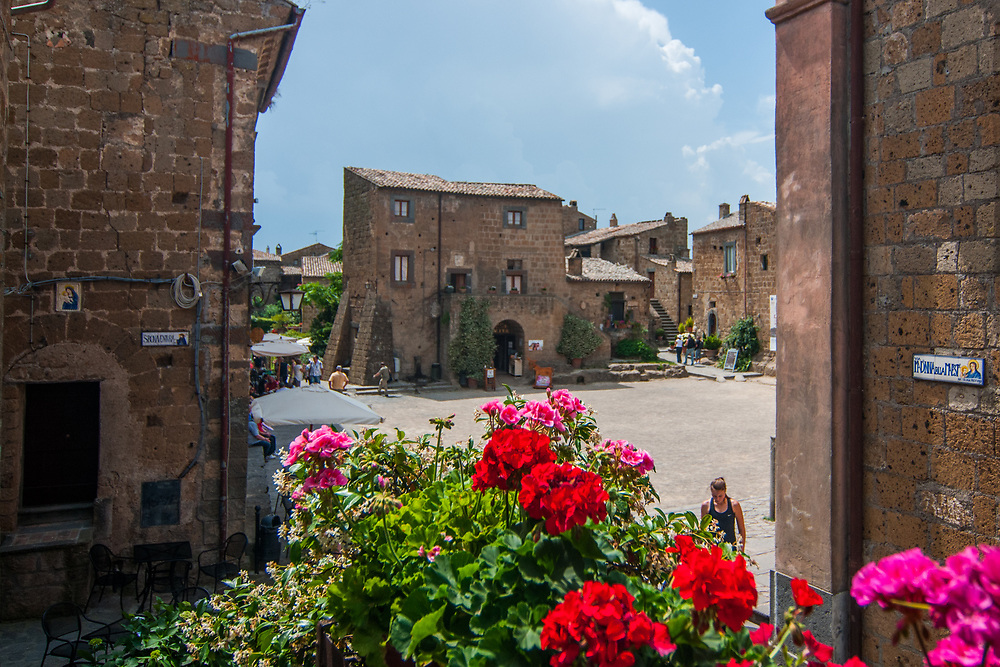 """A view of San Donato square in the village of Civita di Bagnoregio.<br /> Civita di Bagnoregio is a town in the Province of Viterbo in central Italy, a suburb of the comune of Bagnoregio, 1 kilometre (0.6 mi) east from it. It is about 120 kilometres (75 mi) north of Rome. Civita was founded by Etruscans more than 2,500 years ago. Bagnoregio continues as a small but prosperous town, while Civita became known in Italian as La città che muore (""""The Dying Town""""). Civita has only recently been experiencing a tourist revival. The population today varies from about 7 people in winter to more than 100 in summer.The town was placed on the World Monuments Fund's 2006 Watch List of the 100 Most Endangered Sites, because of threats it faces from erosion and unregulated tourism."""