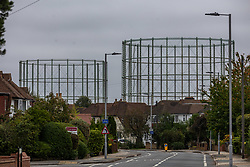 Licensed to London News Pictures. 07/10/2021. London, UK. Disused gas holders which were used in the 1930's to store domestic gas for local homes, tower over houses in Motspur Park south-west London as analysts predict that household energy bills could soar by £400 by next year as the wholesale price of gas hits new highs. Industry leaders have also warned that the high gas price, HGV lorry driver shortage and petrol stations running empty will have a kock-on effect and lead to higher prices for food in supermarkets. Photo credit: Alex Lentati/LNP