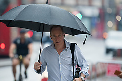 © Licensed to London News Pictures. 13/08/2020. London, UK. A man carrying an umbrella makes his way through a downpour of rain on Kensington High Street, West London as the UK experiences thunderstorms and heavy rainfall following days of sunshine and high temperatures. Photo credit: Ben Cawthra/LNP