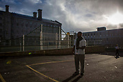 A prisoner stands near the main excercise yard. HMP/YOI Portland, Dorset. A resettlement prison with a capacity for 530 prisoners. Portland, Dorset, United Kingdom.