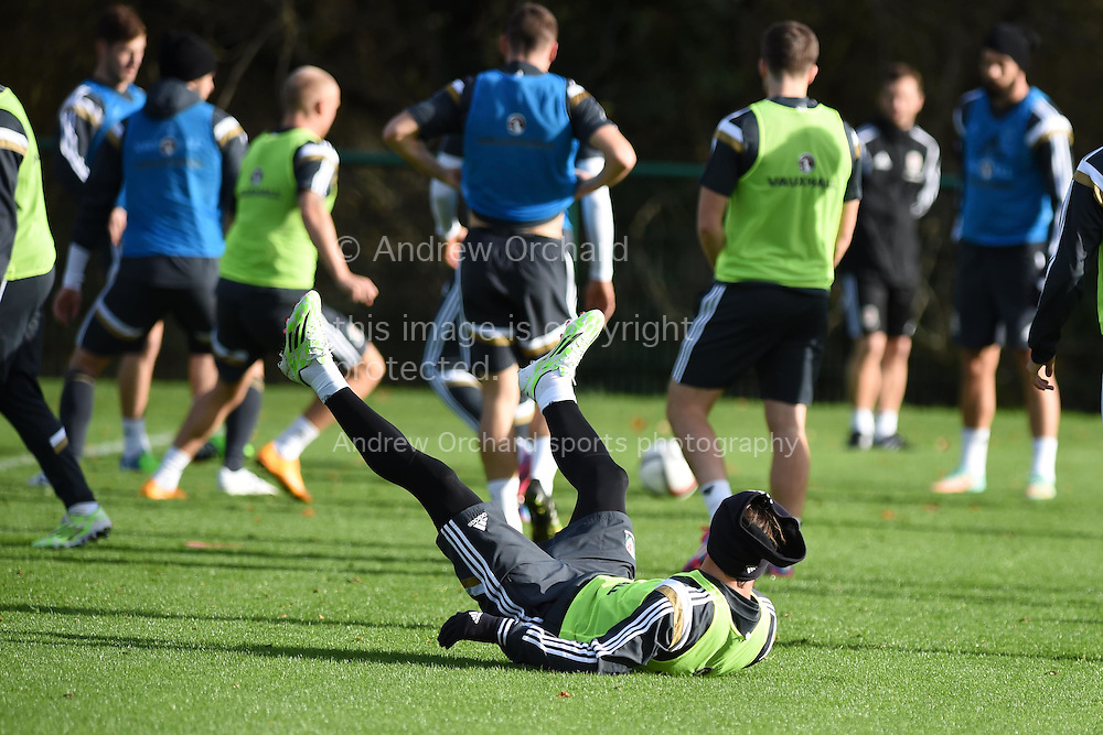 Gareth Bale of Wales takes a tumble during Wales football squad training at the Vale Resort, Hensol, near Cardiff , South Wales onWed 12th November 2014. The team are training ahead of their Euro 2016 qualifying match against Belgium on the weekend.  <br /> pic by Andrew Orchard, Andrew Orchard sports photography.