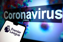 The Premier League logo seen displayed on a mobile phone with an illustrative model of the Coronavirus displayed on a monitor in the background. Photo credit should read: James Warwick/EMPICS Entertainment