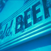 Cold Beer painted signage on side of liquor store. Strong diagonal, cross-processed film.