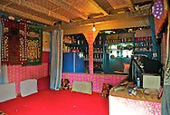 The interior of one of the houses on the Dal Lake with traditional and Islamic carpets decorating the walls and the floor.