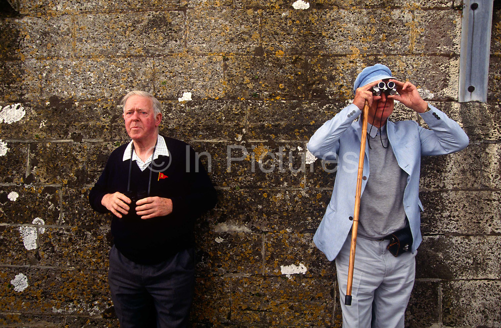 Two elderly gentlemen watch the yacht racing during the Cowes week regatta, the annual sailing competitions held annually every August on the Isle of Wight. Cowes Week is one of the longest-running regular regattas in the world. With 40 daily races, up to 1,000 boats, and 8,500 competitors ranging from Olympic and world class professionals to weekend sailors, it is the largest sailing regatta of its kind in the world. Having started in 1826, the event is held on the Solent (the area of water between southern England and the Isle of Wight made tricky by strong double tides), and is run by Cowes Week Limited in the small town of Cowes on the Isle of Wight.