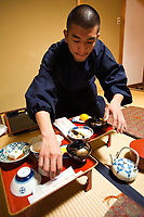 """Novice monk serving temple food or Shojin Ryori, vegetarian cuisine at its finest consisting of pickled, seasonal vegetables, a variety of tofu dishes artfully arranged on lacquerware.  Staying in a temple overnight, especially in Koyasan, is one of the best ways to get to know Japanese culture.  Part of this is experiencing """"shojin ryori"""""""