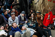 Young people take occupation of Oxford Circus. Peaceful demonstration in central London by protesters during the TUC union march against cuts, Saturday March 26th 2011. Around 400,000 people joined the TUC's March for the Alternative to oppose the coalition government's spending cuts. Teachers, nurses, midwives, NHS, council and other public sector workers were joined by students and pensioners to bring the centre of the capital to a standstill and to make their point that the current coalition government is making cuts too fast which they suggest will have a catastrophic effect on jobs and economic recovery.