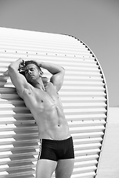 sexy muscular man relaxing against a metal structure in White Sands, NM