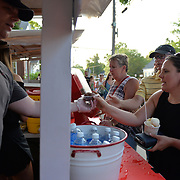YARMOUTH, Maine --  7/21/17 --   Chris Bolling of Sabbaths delivers a cold ice cream treat to Erica Troy at the North Yarmouth Academy boosters booth on Friday night before the Clam Festival Parade in Yarmouth. The Yarmouth Clam Festival parade drew thousands of visitors from around the region. Photo by Roger S. Duncan for the Forecaster.