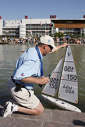 Stock photo of a man preparing to sail his radio controlled boat on the pond