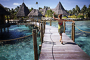 A woman runs down a pier on top of clear ocean waters off the coast of Tahiti
