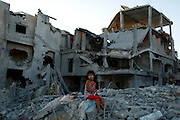 A girl sits on the ruins of her family's home that witnesses say was destroyed by Israeli airstrikes in the Beit Hanoun neighbourhood in Gaza City.