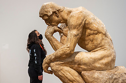 """© Licensed to London News Pictures. 11/05/2021. LONDON, UK. A staff member poses with """"The Thinker, Monumental"""", 1903, by Auguste Rodin. Preview at Tate Modern of """"The Making of Rodin"""", a major new exhibition of over 200 sculpture works by Auguste Rodin, many of which have never been shown outside France. The exhibition marks the reopening of the museum as the UK government eases certain coronavirus lockdown restrictions and is open 18 May to 21 November.  Photo credit: Stephen Chung/LNP"""