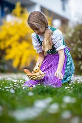 THEMENBILD - Ein Mädchen in Trachtund mit einem Osternest und Schokolade-Hasen auf einer Blumenwiese, aufgenommen am 10. April 2020, in Graz // a girl in traditional austrian dress and a face mask is seeking for a easter present in a flower meadow on 10 April 2020. EXPA Pictures © 2020, PhotoCredit: EXPA/ Erwin Scheriau