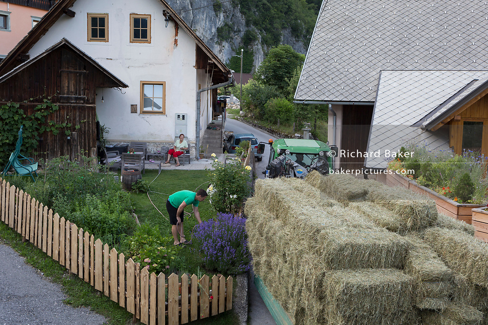 A trailer laden with freshly cut grass squeezes between walls in a rural Slovenian village, on 19th June 2018, in Bohinjska Bela, Bled, Slovenia.