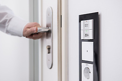 Man's hand opening door protected with central security system, Munich, Bavaria, Germany