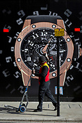 A courier walks an empty trolley past a construction hoarding of a watch outside the new Richard Mille shop in New Bond Street, on 25th February 2019, in London, England.