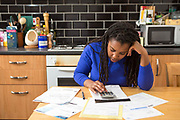 A young lady sits at her kitchen table at home checking over the household bills. Dealing with debt. Household utility bills making it difficult for a British<br /> home owner to afford. Difficulty paying gas and electricity bills is common<br /> as the economic downturn makes personal finances feel the pinch. London, UK.