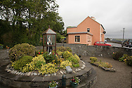 Statue at St. Brigid's Well, Liscannor, County Clare, Ireland with pub in th ebackground on Monday, July 2, 2007. (Photo/John Froschauer).
