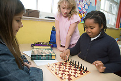 Primary school children playing a game of chess in an after school club,