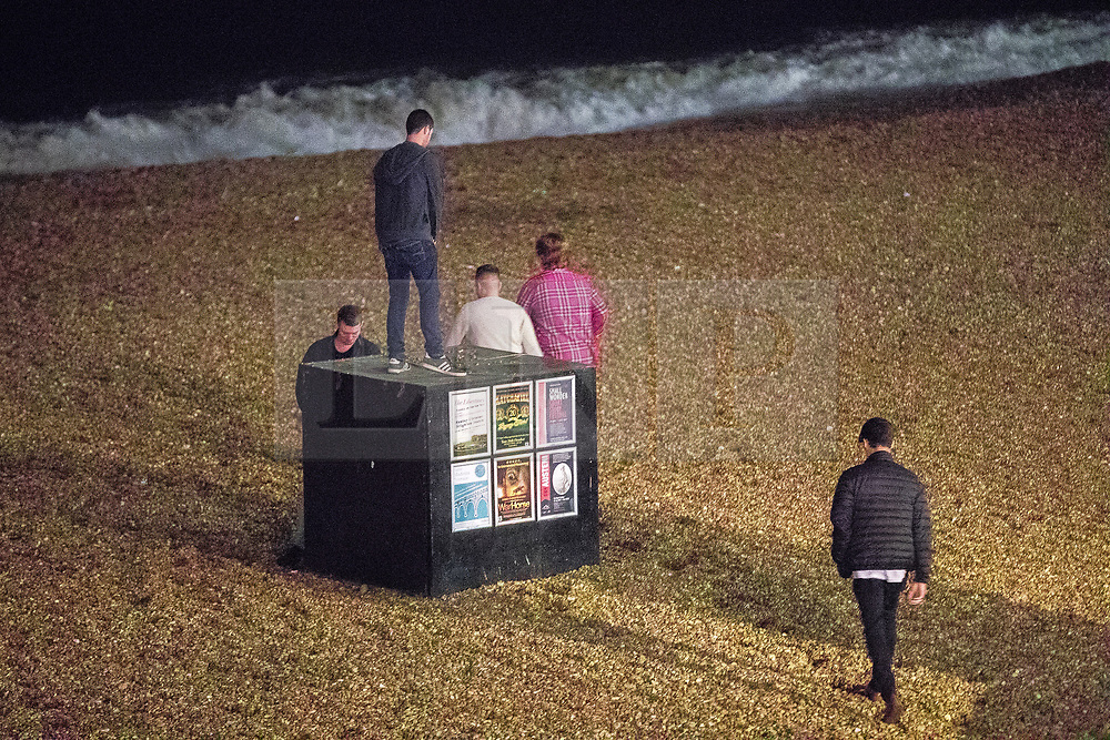 © Licensed to London News Pictures . 26/09/2017. Brighton, UK. A group of men walk out on to the shingles of Brighton beach . Revellers at the end of a night out in Brighton during Freshers week , when university students traditionally enjoy the bars and clubs during their first nights out in a new city . Photo credit: Joel Goodman/LNP