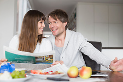 Couple having breakfast and reading newspaper together, smiling