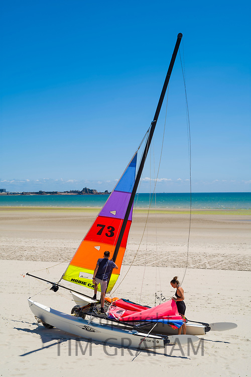 Young people preparing Hobie Cat catamaran on St Aubin's sandy beach, Jersey, Channel Isles