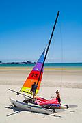 Young people preparing Hobie Cat catamaran on St Aubin's sandy beach, Jersey, Channel Isles