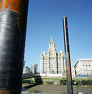 The Liver Building at the Pier Head on the river Mersey in Liverpool, seen through the pillars of the newly-constructed liner landing stages. The Mersey is a river in north west England which stretches for 70 miles (112 km) from Stockport, Greater Manchester, ending at Liverpool Bay, Merseyside. For centuries, it formed part of the ancient county divide between Lancashire and Cheshire.