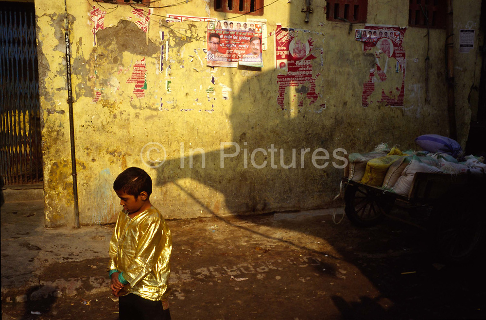 A performers son in a gold shirt, Shadipur Depot, New Delhi, India<br /> The Kathiputli Colony in the Shadipur Depot slum is home to hundreds of (originally Rajasthani) performers. The artistes who live here - from magicians, acrobats, musicians, dancers and puppeteers are often international renowed by always return to the Shadipur slum.
