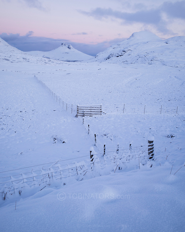 A heavy snowfall is revealed as dawn gently appears above Ben More and the Coigagh mountains at Drumrunie in Assynt, Scotland.