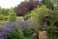 A stone sculpture in the shape of a fruit basket and Campanula lactiflora at the entrance to the walled Autumn Garden at Newby Hall, Ripon, North Yorkshire